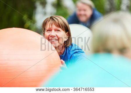 Vital senior woman is exercising with a gym ball in rehab course in the park