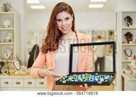 Smiling shop assistant in jewelry store presents necklaces in jewelry box