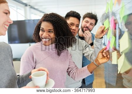 Group of trainees in a training course in creative brainstorming with sticky notes
