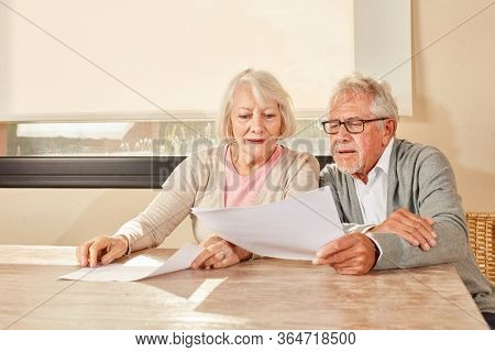 Senior couple looks together on a contract for retirement or insurance