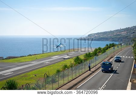 Man Watching Airplane Taking Of From Runway Of Funchal International Airport, Scenic Ocean View And