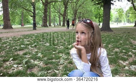 Kid In London Park, Bored Child Resting On Grass By Buckingham, Alone Little Girl Not Playing Outdoo