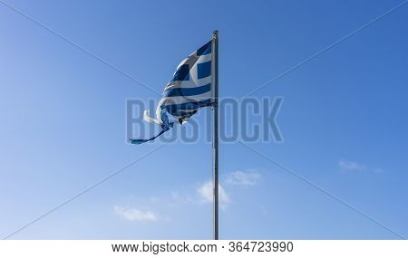 Tattered Greek Flag In The Wind With Blue Sky