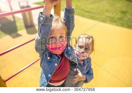 Happy Children In Eastern Europe Playing With Face Masks On Playground During Quarantine Covid19. Sl