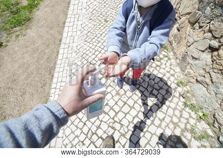 Father Using Wash Hand Sanitizer Gel Pump Dispenser Outdoors. Wide Angle View