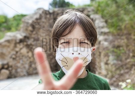 Little Boy Holds Up Two Fingers For Victory Over Covid-19 Pandemic. He Is Wearing Face Mask With Chi