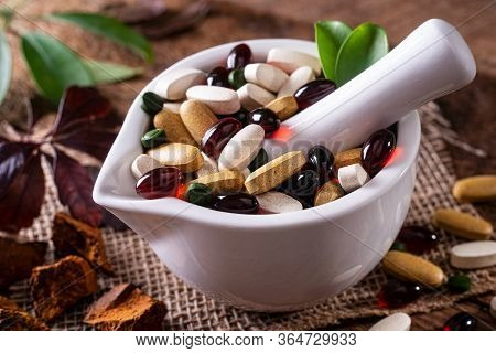 Natural Organic Nutritional Supplements In A Pharmaceutical Mortar And Pestle.