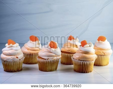 Six, 6, Yellow Cupcakes Lined Up With Orange And White Creamsicle Frosting Swirled Up High And An Or