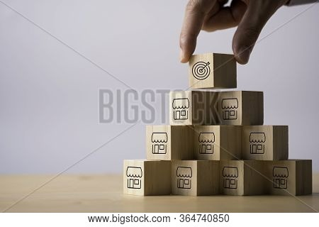 Hand Putting Target On Several Shop Which Print Screen On Wooden Cube. Expand Business Investment An