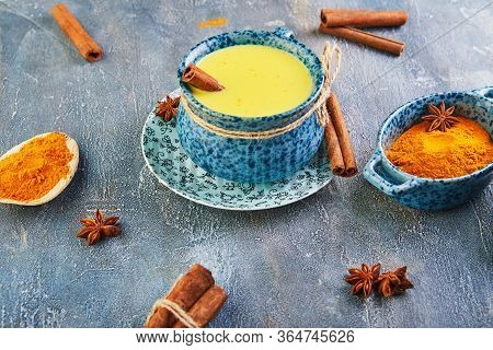 Golden Milk With Turmeric, Cinnamon Sticks, Turmeric And Anise On A Gray Cement Background. Turmeric