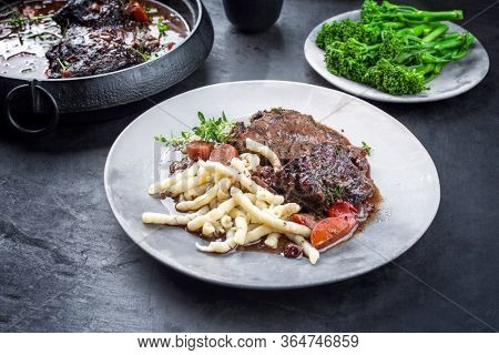 Traditional German braised beef cheeks in brown red wine sauce with noodles and broccoli offered as closeup on a modern design plate and stewpot on an old rustic board