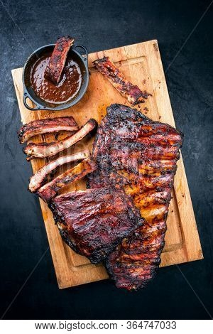 Barbecue veal spare loin ribs St Louis cut with hot honey chili marinade burnt as top view on a rustic wooden cutting board