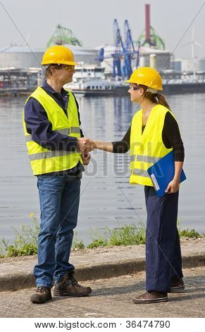 Two dockers, a man and a woman shaking hands in an industrial harbor, wearing the necessary safety gear poster