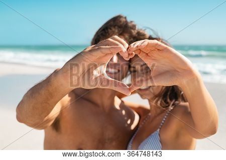 Happy husband and wife gesturing heart with fingers at sea during honeymoon. Young couple showing heart shape with hand gesture. Couple looking through a heart shape made with their fingers at beach.