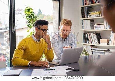 Mature and young businessmen discussing during meeting in boardroom. Business executive working with apprentice in creative office. Multiethnic business team in smart casual working together on laptop