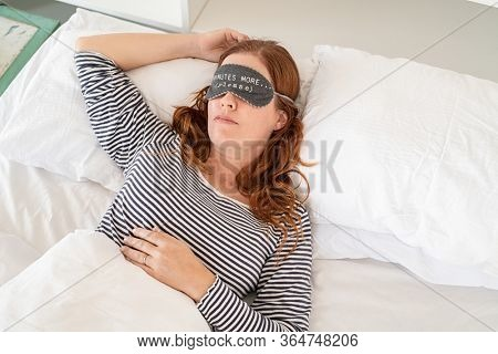 Top view of mature woman sleeping on bed. Beautiful sleepy middle aged woman wearing funny eye mask. High angle view of woman in pajamas dreaming on bed with eye mask with five minutes more text.
