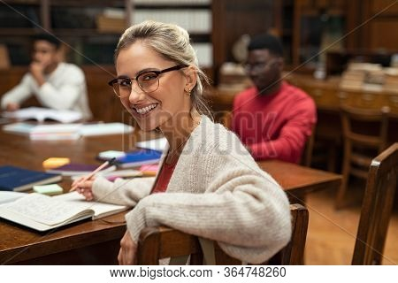 Portrait of university female student studying in library. Happy young woman wearing spectacles studying in college library and looking at camera. Satisfied girl studying for exam.