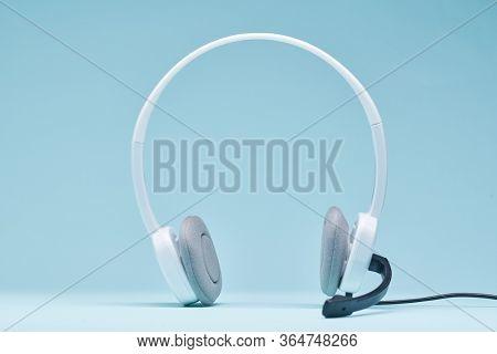 White headphones isolated on blank blue background