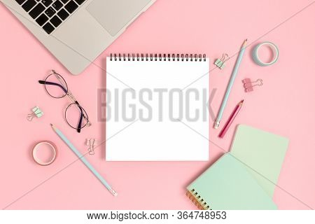 Blank Notepad Mockup. Top View Of Laptop And Stationery On A Pink Pastel Background. Workspace Conce