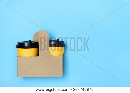 Yellow Paper Cups In Craft Cup Holder And Light Blue Background. Flatlay. Coffee To Go Concept. Plac