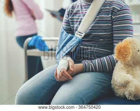 Cute Girl With Arm Brace And Teddy Bear