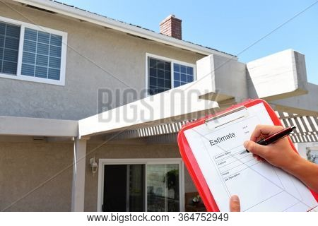 Contractor with clipboard writing an estimate for outdoor home improvements.