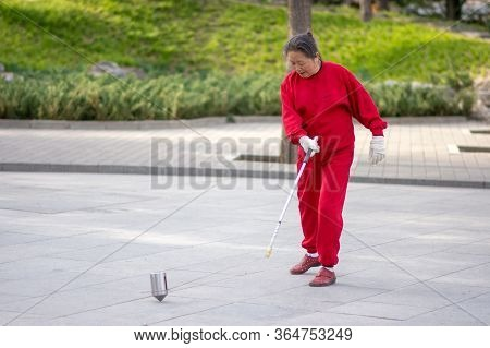 Beijing / China - April 3, 2016: Old Chinese Woman Whipping Spinning Tops, Traditional Chinese Game