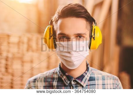 Portrait Of Confident Man Carpenter In Medical Face Mask And Hearing Protectors At Wooden Workshop.