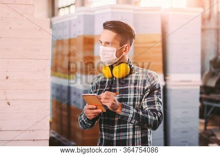 Portrait Of Man Supervisor In Medical Face Mask And Protective Headphones Checking Wood Material Inv