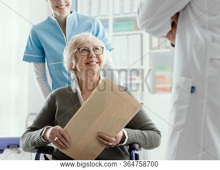 Senior Patient On Wheelchair With Medical Staff