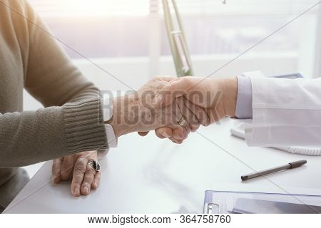 Doctor And Senior Patient Shaking Hands In The Office