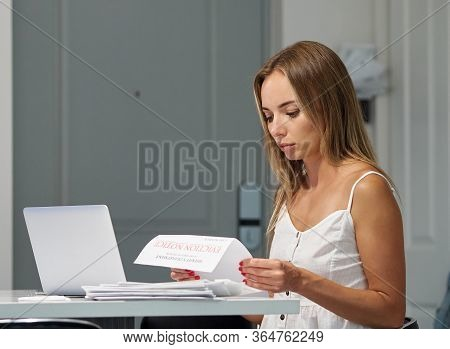 Worried Female With Laptop Reading Eviction Letter In Apartment