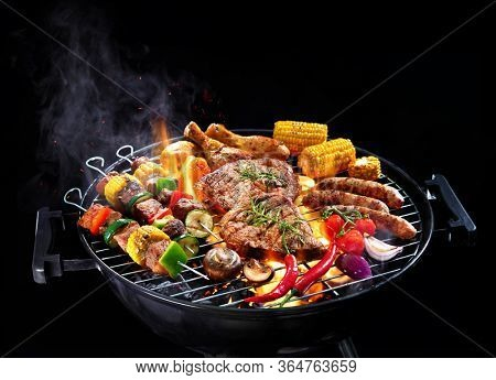 Assorted delicious grilled meat with vegetables on barbecue grill with smoke and flames isolated on black background