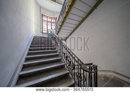Stairs In Old Apartment Building Entrance With Symmetrical Staircase And High Ceilings