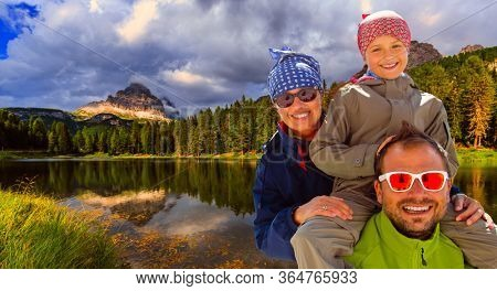 Happy family outdoor adventure with kid in Dolomites mountain in summer time in Italy. Concept of travel, friendly family.