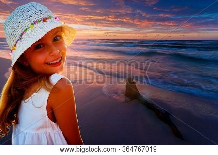Young girl at the beach enjoying  sunset view over the Baltic Sea, Poland