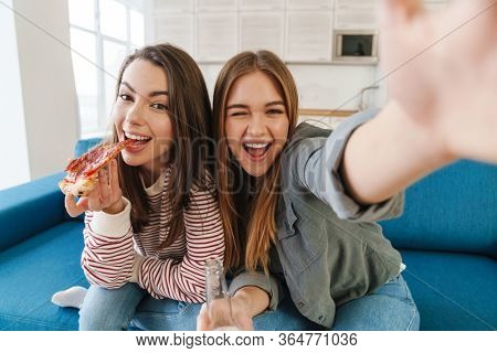 Photo of young joyful two girls eating pizza and drinking bear while taking selfie photo in kitchen