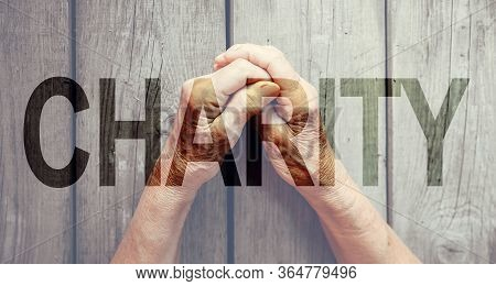 Charity Fill Text, Old Hands, Wooden Background. Elderly People Health, Hunger, Poorness, Need. Team