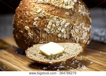 Fresh Loaf Of Mulit Grain Bread, With A Slice Cut And Topped With A Pat Of Butter