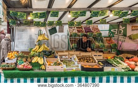 Paris, France -- November 4, 2017 -- A Parisienne Merchant Works At His Fruit And Vegetable Stand On