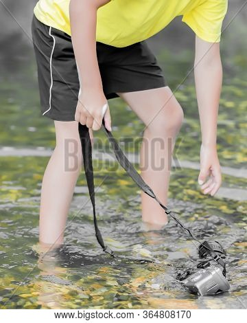 A Child Stands In The River On Outdooor And Destroys A Mirrorless Camera. The Concept Of Obsolescenc
