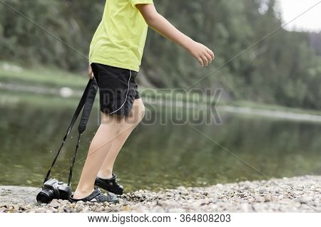 A Boy Stands In The River On Outdooor And Destroys A Mirrorless Photo Camera. The Concept Of Obsoles