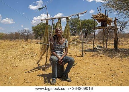 Motswana, African woman in the bush selling brooms, Kalahari in Botswana