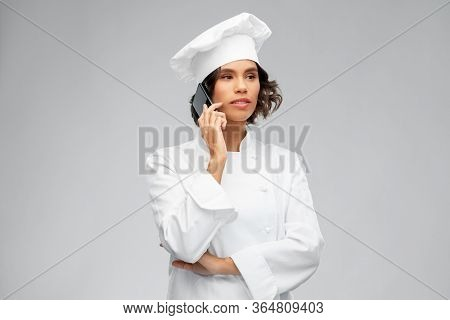 cooking, culinary and people concept - female chef in toque calling on smartphone over grey background