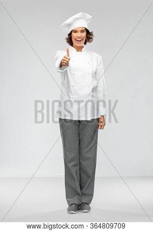 cooking, gesture and people concept - happy smiling female chef in toque showing thumbs up over grey background