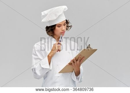 cooking, culinary and people concept - female chef in toque with clipboard and pen over grey background