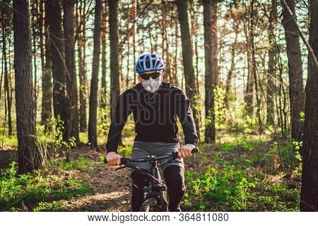 Cyclist Wearing Pollution Mask. Young Guy In Respirator With Filter Pm 2.5 With Ride On Bike In Park