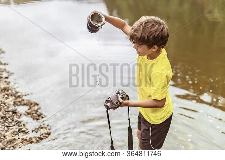 A Child Stands In The River On Outdooor And Destroys A Mirrorless Photo Camera. The Concept Of Obsol