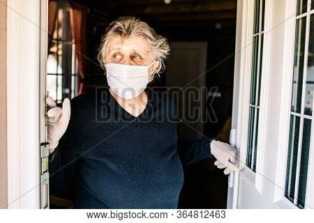 Elderly Woman, Grandma Wearing A Mask Standing At The Door Looking Outside. Corona Virus Outbreak