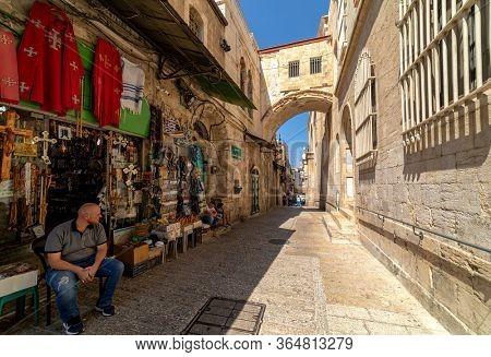 JERUSALEM, ISRAEL - JULY 16, 2018: Seller sitting in front of souvenir shop on Via Dolorosa street in Old City of Jerusalem - capital of Israel, famous and popular tourist travel destination.